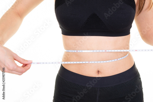 Fotografía  fit slim young woman waist with measuring tape over white background
