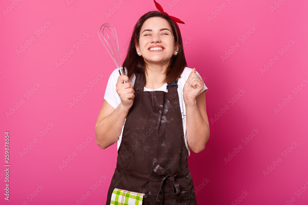 Fototapety, obrazy: Smiling cheerful girl clenches fists with kitchen equipment in right hand, wears work clothing, being in high spirits. Dark haired slender female takes pleasure in process of cooking, develops skills.
