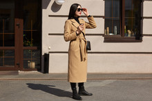 Young Pleasant Blackhaired Woman Looks In Distance, Tries To Choose Better Road To Have Long Walk. Fashionable Tall Lady Wears Long Beige Stylish Coat With Leather Bag And Black Sunglasses.