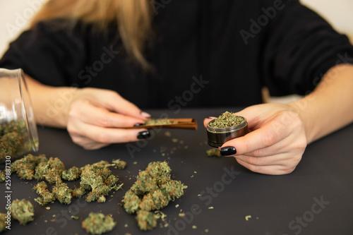 Stampa su Tela  Woman rolling a marijuana joint