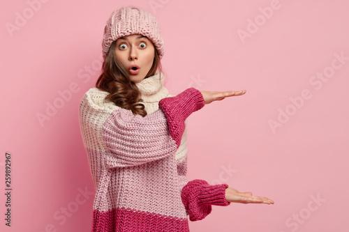 Fotografie, Obraz  Surprised emotional curly woman demonstrartes big size with both hands, shapes something huge, wears hat and loose winter jumper, stands in studio over pink background