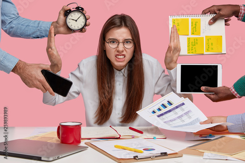 Overworked young employee refuses all things, frowns face in annoyance, sits at desktop with paper documents and notepad, isolated over pink background. Female workes bothered by many questions