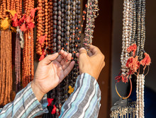 A Man's Hand, Fingering Indian Beads Rudraksha And Beads Of Lotus Seeds, Bright Orange Beads, Mala, Silk Tassels And Pearls.