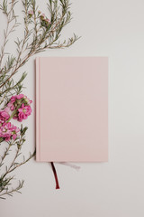 Pink notepad and flowers on a white background. Diary, top view, flatlay