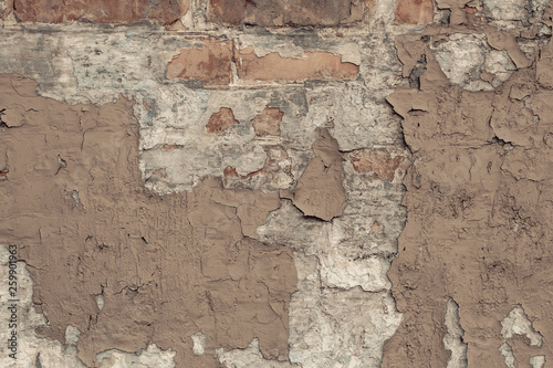 Spoed Foto op Canvas Oude vuile getextureerde muur Peeling beige paint on a brick wall in vintage style. Vintage house facade. Empty space. Grunge background. old wall cement background. Light-brown shabby concrete wall texture.