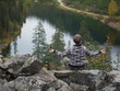girl sitting in Lotus position with his back against a large mountain lake surrounded by forest and mountains.