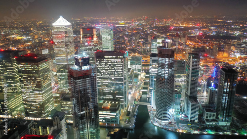 Fotografia  Aerial drone night shot from iconic Canary Wharf illuminated skyscrapers busines