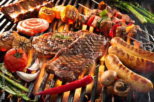 Delicious grilled meat with vegetables sizzling over the coals on barbecue Canvas Print