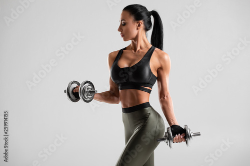 Keuken foto achterwand Fitness Fitness woman doing exercise for biceps on gray background. Muscular woman workout with dumbbells