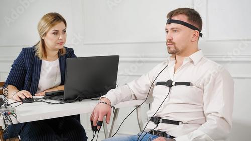 Fényképezés polygraph technician reads questions from a laptop