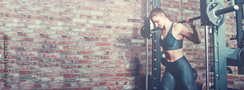 Leinwand Poster Athletic young woman doing lunges with the smith machine against brick walll with window at gym