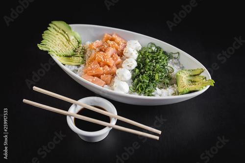 Photo  Nikkey gohan with white rice, salmon, avocado and philadelphia cheese on a black