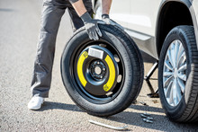 Road Assistance Worker In Uniform Changing Car Wheel On The Highway, Close-up View