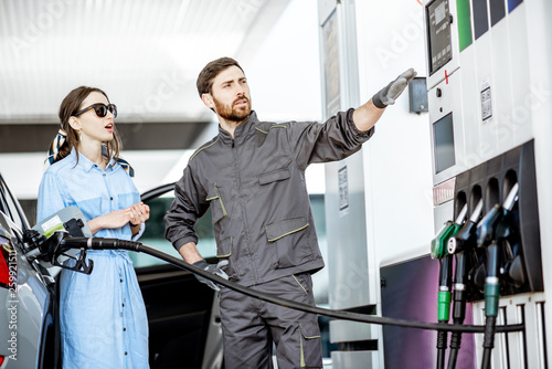 Fotografija Young woman client with gas station worker refueling car at the gas station