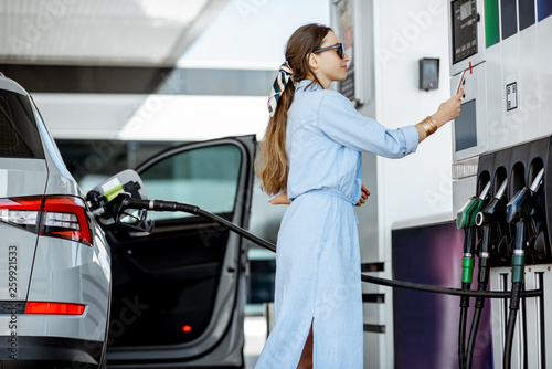 Fotografia Woman paying with phone for gasoline, photographing bar code on the gas station