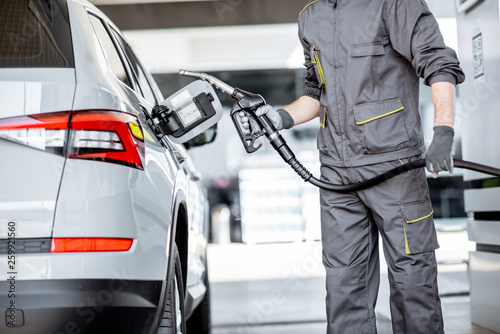Fotografia Gas station worker in workwear refueling luxury car with gasoline holding fillin