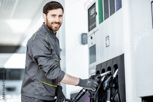 Stampa su Tela Gas station worker in uniform taking filling gun, refueling car at the gas stati