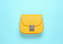 Yellow Leather Mini Bag On Blue Background. Minimalism Fashion Concept. Top View