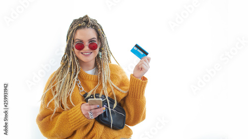 Extravagant plus size young woman with glasses holding a smartphone and a credit card in her hands.