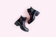 Leinwanddruck Bild - Black female boots on pink background. Flat lay, top view minimal background. Fashion blog or magazine concept.