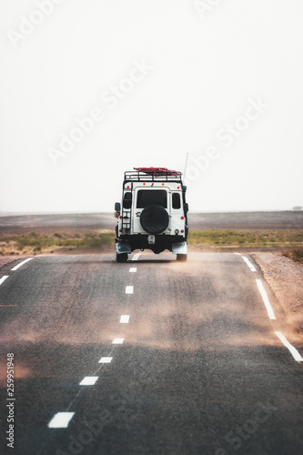 On the road to Merzouga, car travels the road to the Sahara desert of Morocco during a sandstorm Canvas Print