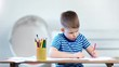 Medium shot confident little boy drawing picture on paper using colored pencils sitting on table