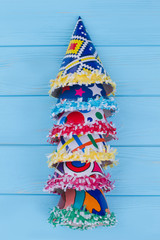 Row of party hats, vertical image. Set of different Birthday caps on color wooden background, top view. Kids accessories for party celebration.