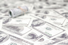 US Dollars Rolled Up And Tightened With Band Lies On A Lot Of American Banknotes With Blurred Background