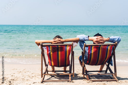 Foto  Romantic lovers young couple relaxing sitting together on the tropical beach and looking to the sea