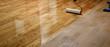 Leinwanddruck Bild - Lacquering wood floors. Worker uses a roller to coating floors.