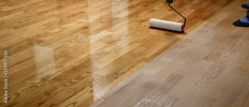 Fotografie, Obraz Lacquering wood floors. Worker uses a roller to coating floors.