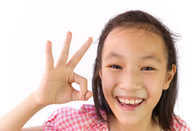 Portrait Of A Happy Asian Little Girl Showing Ok Sign With Fingers Isolated On White Background, Closeup Child Is Smiling