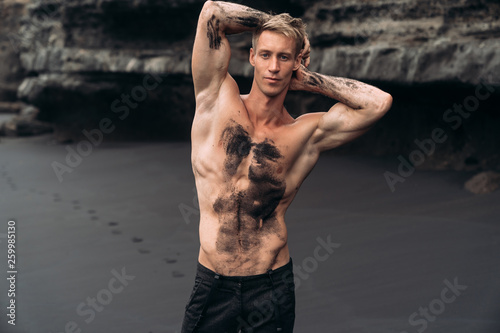 Fototapety, obrazy: Sexy fitness male model in black pants and shirtless posing on black sandy beach