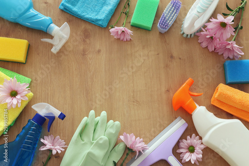 Fotografia Spring cleaning concept with supplies over wooden background