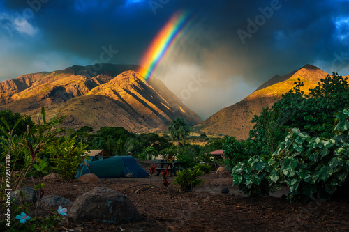 Rainbow over the mountains and tent set in the camping Canvas Print