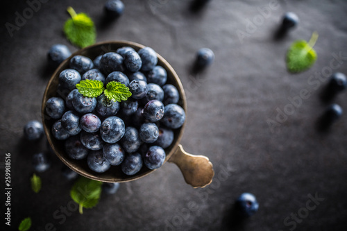 Vintage bowl full of fresh blueberries with herbs.