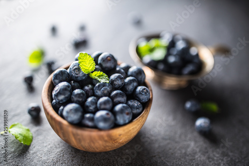 Photo  Wooden bowl full of fresh blueberries with herbs