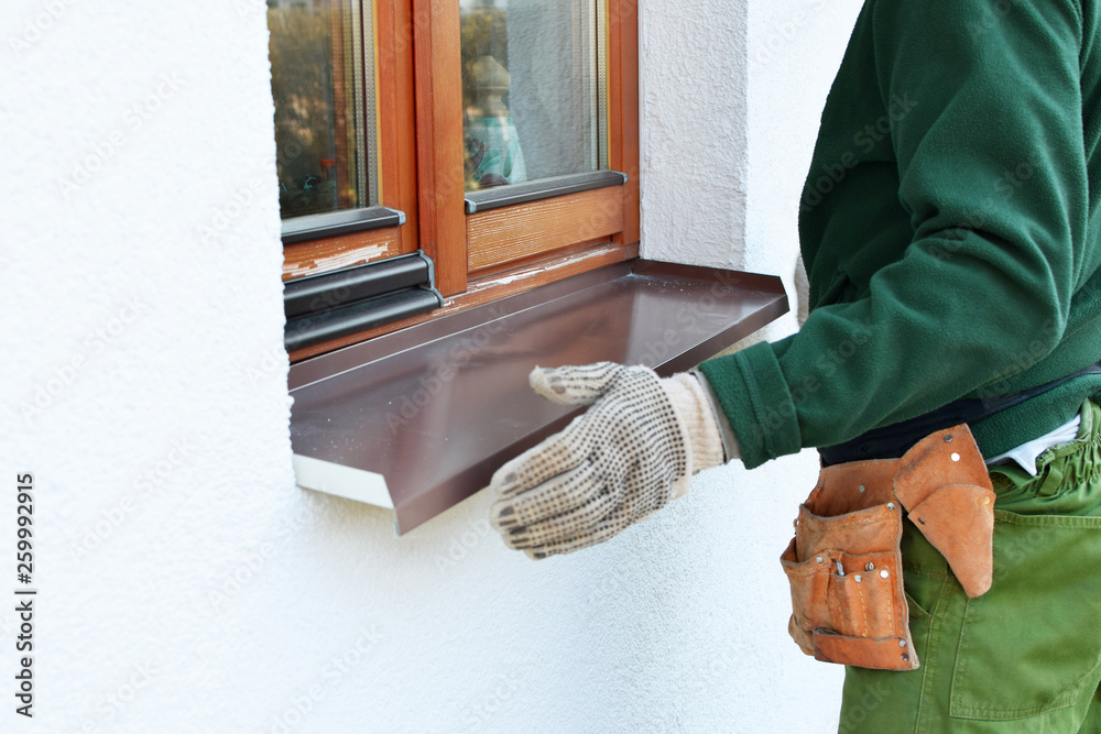 Fototapety, obrazy: Man worker in protective gloves installing sill on external wooden window frame on white house facade. Sill installation process. Exterior design, building, home improvement, diy concept.