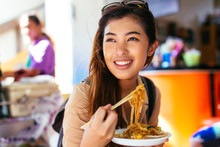 Young Asian Tourist Woman Eati...