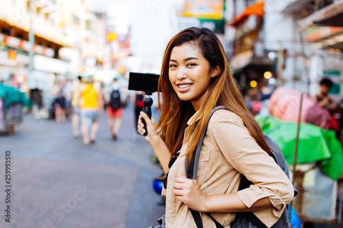 Photo Young Asian female tourist woman holding a gimbal with smartphone and recording videos for blog