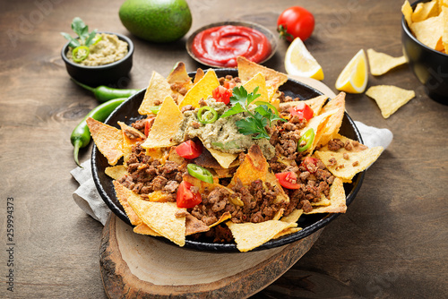 Cuadros en Lienzo Corn chips nachos with fried minced meat and guacamole on wooden background