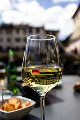 Foto  White italian wine on a wineglass on an outdoor restaurant terrace