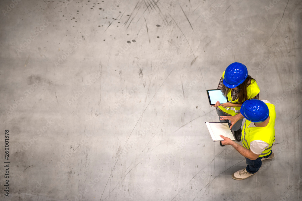 Fototapeta Top view of two industrial workers wearing hardhats and reflective jackets holding tablet and checklist on gray concrete background. Group of engineers sharing ideas about the project.