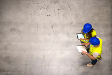 Top View Of Two Industrial Workers Wearing Hardhats And Reflective Jackets Holding Tablet And Checklist On Gray Concrete Background. Group Of Engineers Sharing Ideas About The Project.