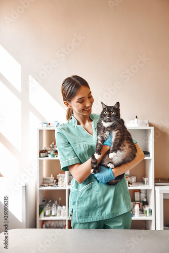 Are you scared? Pleasant young female vet holding a big black cat and smiling while looking at him while standing at the veterinary clinic Wall mural
