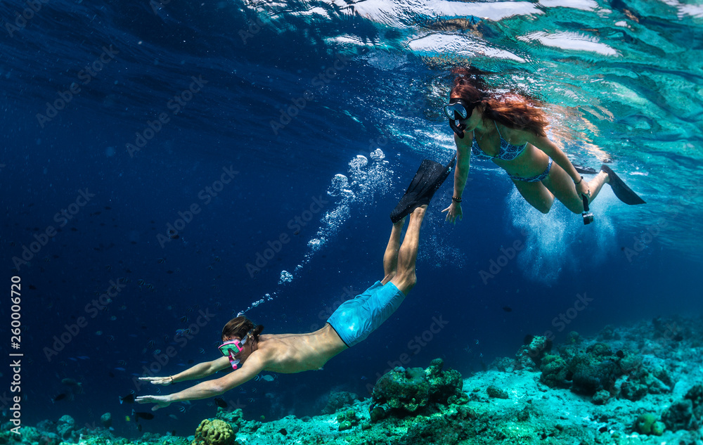 Fototapeta Young couple snorkeling and do skin diving on the coral reef edge in tropical waters of the Maldives