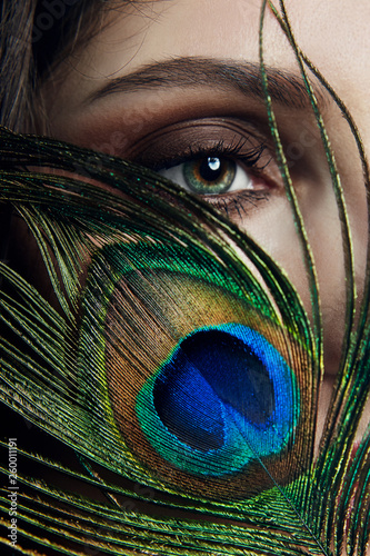 Eastern Arab woman with a peacock feather in her hands near her face Canvas-taulu