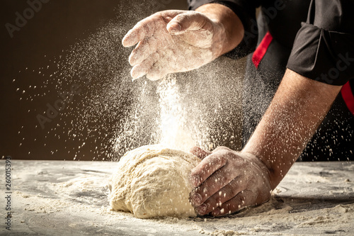 Chef hands cooking dough on dark wooden background. White flour flying into a...