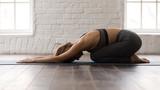 Young woman practicing yoga, lying in Child pose, Balasana exercise