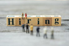 "Miniature People, Candidates And Wooden Word Block ""HIRING"". Human Resource Concept, Recruiting, Hiring Process."